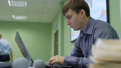 Young man working at a laptop in the audience. Beginning businessman carefully Stock Footage