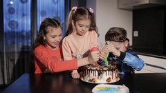 Three little girls baked a cake and decorate it with cream color Stock Footage