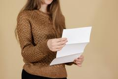 Girl reading blank white flyer brochure booklet. Leaflet presentation. Pamp.. Stock Photos