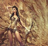 Glamorous woman posing over the huge golden wing Stock Photos