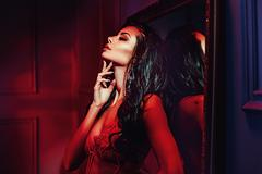 Seductive brunette woman in the red place Stock Photos