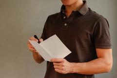 Man makes notes in blank white flyer brochure booklet. Leaflet presentation.. Stock Photos