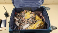 Girl is packing the suitcase with lots of money for holiday or weekend trip Stock Footage