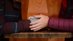 Closeup Portrait of Hands of a Couple Holding Coffee Cup Over a Table in Winter Stock Footage