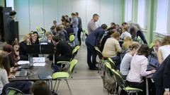 Students divided in several groups sitting at the long tables and carrying out Stock Footage