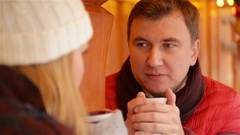 Smiling Man in Red Jacket and Maroon Scarf Having Hot Drink and Talking with Stock Footage