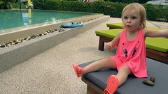 Cute little girl gesticulates near pool Stock Footage