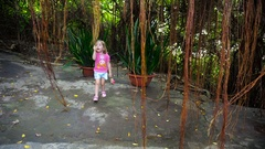 A child plays in the tropical jungle with lianas. Stock Footage