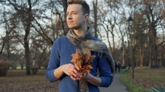 Handsome man walking in the autumnal park and holding bunch of leaves, steadycam Stock Footage