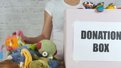 Girl with box of toys ready for donation Stock Footage