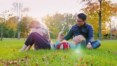 Interracial Young couple resting in a park with a dog. Asian man stroking a dog Stock Footage