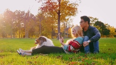 Young multi-ethnic couple relaxing in the park with his dog. Caucasian woman Stock Footage