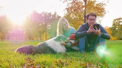 Young multi-ethnic couple relaxing in the park with his dog. Asian man looking Stock Footage
