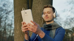 Happy man listening music and doing selfies on tablet in the park, steadycam sho Stock Footage