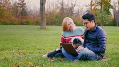 A young Asian man working with a laptop in the park. Near an attractive woman Stock Footage