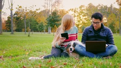 Young people relaxing in a park. Asian man uses a laptop, woman reading Stock Footage
