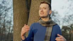 Man standing in the park and telling something to the camera, steadycam shot Stock Footage