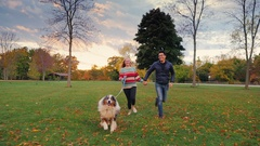 Asian man and Caucasian woman running in the park with his dog. Happy together Stock Footage