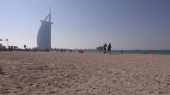 People in Dubai beach walk on shoreline seaside landscape Burj al Arab view 4K Stock Footage