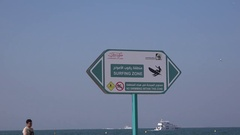 Dubai beach surfing zone swimming not allowed sigh luxury yachts sailing water Stock Footage