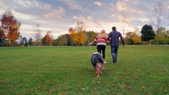 Have fun with your beloved dog. Young multi-ethnic couple running in the park Stock Footage