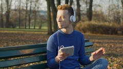 Man listening music while sitting in the park and moving to the melody, steady Stock Footage