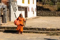 Nepali aged pilgrim in orange robe in the temple Stock Photos