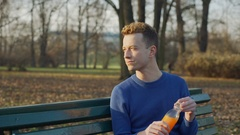 Man receives message on smartphone while drinking juice in the park, steadycam  Stock Footage