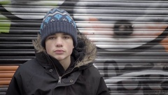 Teenage boy sitting in front of a graffiti covered door on a cold winter day. 4K Stock Footage