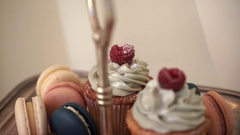 Chocolate muffins with raspberries and multicolored macaroon on a candy bar Stock Footage