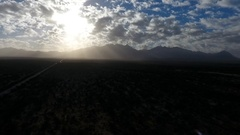 Aerial of a road heading towards mountain peaks and sun rays Stock Footage