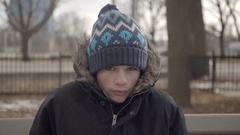 Teenage boy sitting on park bench on a very cold winter day. 4K UHD. Stock Footage