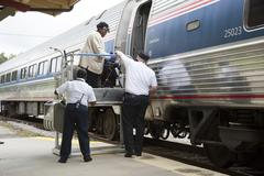Disabled person using a portable lift to enter a railroad train Stock Photos