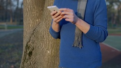 Man in casual, warm clothes browsing internet on smartphone, steadycam shot Stock Footage