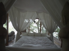 Sleeping girl wakes up. Romantic bed under the canopy. Bedroom in the forest. Stock Footage