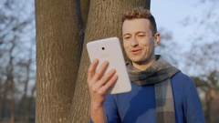 Handsome man standing next to the tree and having a videocall, steadycam shot Stock Footage