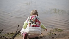 Beautiful child plays in the water with a stick.   Stock Footage