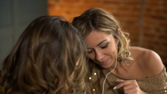 Happy girlfriends listen to music from the phone and laughing Stock Footage