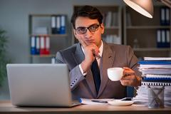 Businessman staying in the office for long hours Stock Photos