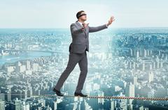Man walking in tight rope blindfold Stock Photos