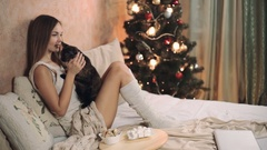 Woman in warm sweater on the bed with cup of coffee in hands, Christmas tree new Stock Footage
