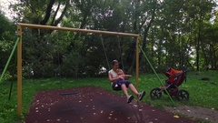Aerial view around the mother swinging her daughter Stock Footage