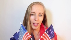 Beautiful American patriotic woman speaks into the camera Stock Footage