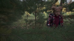 Little girl walking in the forest and looking at the pine branch Stock Footage