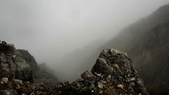 Motion along the rocky terrain in autumn misty mountains Stock Footage