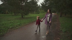 Mother and daughter walking in the autumn park they show something to each other Stock Footage