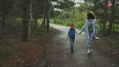 Mother and son walking in the autumn park Stock Footage