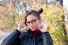"""Girl with glasses shows a hand sign of """"OK"""" Stock Photos"""