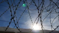 Barbed wire fence at the prison, the sun glare on a background of blue sky Stock Footage