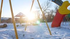 Swing for children swinging on the playground sun glare snow winter Stock Footage